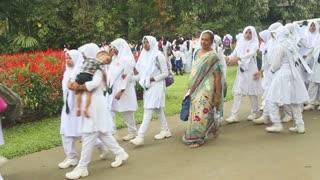 KANDY, SRI LANKA - FEBRUARY 2014: Muslim school girls standing in line in the Botanical Garden in Kandy.