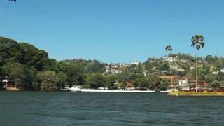 KANDY, SRI LANKA - FEBRUARY 2014: Pan of buddha statue on hill on Kandy lake.