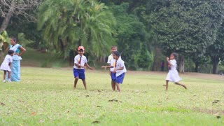 KANDY, SRI LANKA - FEBRUARY 2014: Sri Lankan children in school uniform playing in the Botanical Gardens. All children are required to wear uniforms.