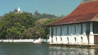 KANDY, SRI LANKA - FEBRUARY 2014: View of house on Kandy lake with Buddha statue in background.
