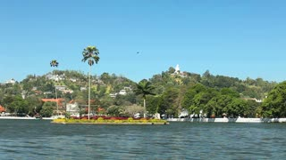 KANDY, SRI LANKA - FEBRUARY 2014: View of Kandy lake and buddha statue on hill.