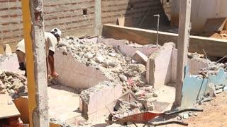 KOSGODA, SRI LANKA - MARCH 2014: Local construction worker with wheel barrow on building site.