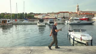 KRK, CROATIA - MAY 4, 2013: Fisherman in old town Krk harbour on May 4, 2013 in Krk, Croatia. Ancient Krk town, is among the oldest cities in Adriatic, continuously inhabited since Roman times.