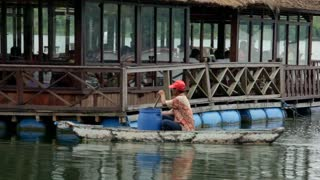 LAKE BATUR, BALI - JANUARY 21: Fisherman delivering fish to restaurant in small boat on Lake Batur on January 21, 2012 in Bali, Indonesia. Fishing is important source of subsistence on the lake.