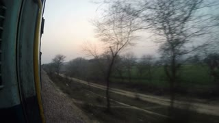 Landscape view through open train door during a slow train ride.
