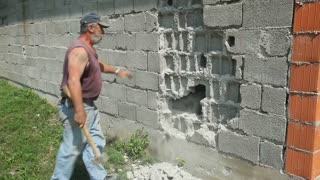 LIKA, CROATIA - JUNE 19, 2013: Worker knocking house wall down on June 19, 2013 in Lika, Croatia. The Serbian population fled and houses abandoned during the croatian war and now being rebuilt.