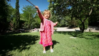 Little girl dancing in garden in summer