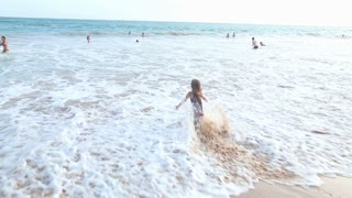 Little girl playing and falling in waves on a beach in Mirissa, Sri Lanka.