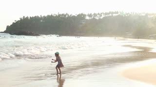Little girl playing in waves on beach in Mirissa in Sri Lanka