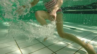 Little girl running underwater in swimming pool making bubbles