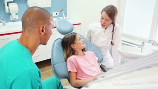 Little girl sitting in the dental chair, talking with dentist and assistant