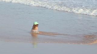 Little girl sitting on beach in Mirissa in Sri Lanka