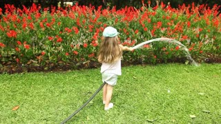 Little girl watering flowers in botanical garden.