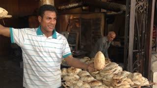 Local man selling egyptian pita bread at Giza