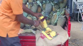 Local man slicing a pineapple at Hikkaduwa market.