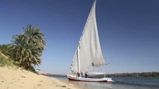 Local people and tourist anchored their felucca on shore of Nile.
