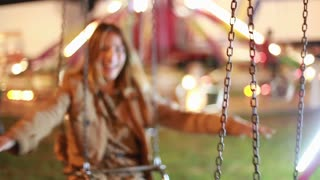 Lovely woman on swing, laughing and enjoying in amusement park