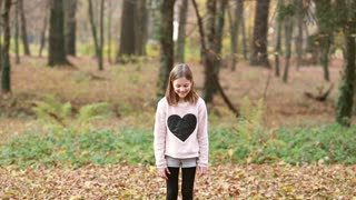Lovely young girl throwing leaves and jumping in park in autumn, slow motion
