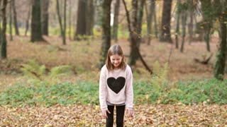Lovely young girl throwing leaves and jumping in park in autumn
