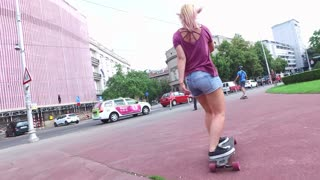 Low angle back view of women longboarding with friends in the city