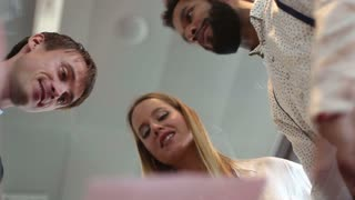 Low angle close up of businesswoman and two male colleagues discussing documents and business plan in office