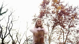Low angle shot of beautiful little girl having fun throwing leaves in the air at park, graded