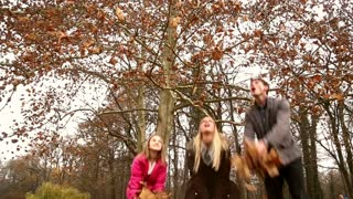 Low angle shot of young happy family throwing leaves in the air in park, slow motion