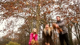 Low angle shot of young happy family throwing leaves in the air in park