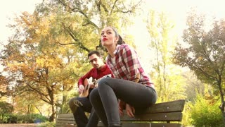 Low angle view of attractive woman singing while man playing guitar, sitting next to her on bench in park, graded
