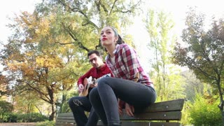 Low angle view of attractive woman singing while man playing guitar, sitting next to her on bench in park