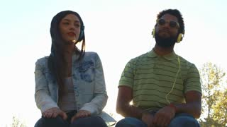 Low angle view of beautiful young couple listening to music with headphones on nice sunny day, graded