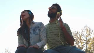 Low angle view of beautiful young couple listening to music with headphones on nice sunny day