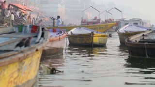 Low angle view of boats at dock in Ganges, with people in background.