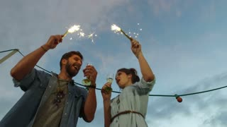 Low angle view of couple holding firework candles and toasting with champagne