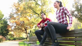 Low angle view of handsome man playing guitar while beautiful young woman dancing to the rhythm, sitting next to him on bench in park, graded