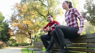 Low angle view of handsome man playing guitar while beautiful young woman dancing to the rhythm, sitting next to him on bench in park