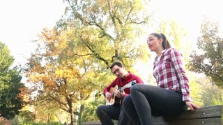 Low angle view of handsome man playing guitar while beautiful young woman singing, sitting next to him on bench in park, graded