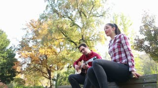 Low angle view of handsome man playing guitar while beautiful young woman singing, sitting next to him on bench in park