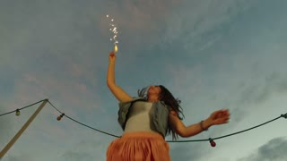 Low angle view of happy woman jumping with firework candle