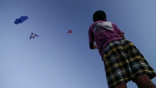 Low angle view of Indian boy kiting at beach in Goa.