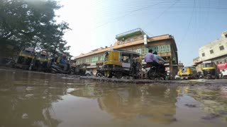 Low angle view of traffic at street in Mumbai, with puddle of water in front.