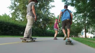 Low angle view of two men and one woman skateboarding at sunset
