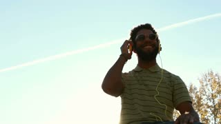 Low angle view of young african american man with headphones listening to music at park, graded