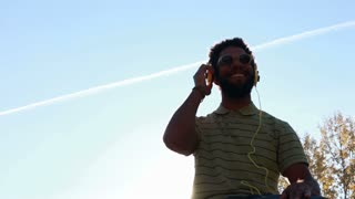 Low angle view of young african american man with headphones listening to music at park