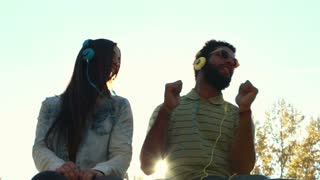 Low angle view of young couple having fun listening to music with headphones on beautiful sunny day, graded