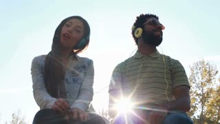 Low angle view of young couple having fun listening to music with headphones on beautiful sunny day, slow motion