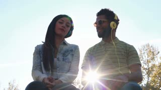 Low angle view of young couple having fun listening to music with headphones on beautiful sunny day