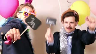Male friends dancing with a sign in love in photo booth