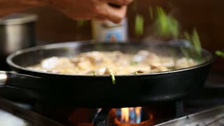 Man adding herbs to meat and sauce boiling in pan.