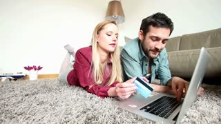 Man and woman lying on carpet in living room while doing online buying